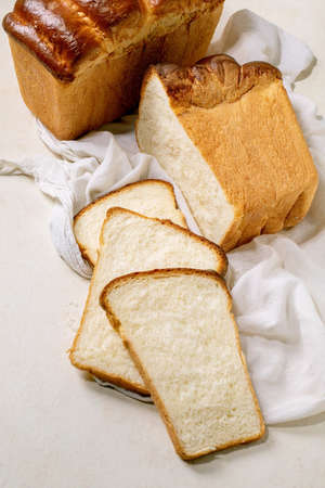 Homemade Hokkaido wheat toast bread whole and sliced on white cloth on table.