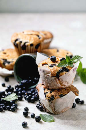 Homemade blueberry muffins in paper cupcake holder in stack decorated by fresh berries and mint leaves on light grey background.