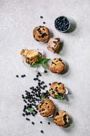 Homemade blueberry muffins in paper cupcake holder decorated by fresh berries and mint leaves on light grey background. Flat lay, copy space 版權商用圖片