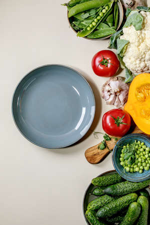 Variety of fresh raw organic vegetables for cooking. Half of hokkaido pumpkin, young green pea, cauliflower, cucumbers and empty plate over beige background. Healthy eating concept. Flat lay, space