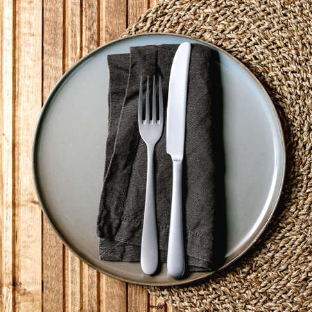 Empty ceramic plate with fork and knife on textile napkin on knitted straw round napkin over wooden plank background. Flat lay, space 版權商用圖片