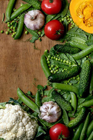 Variety of fresh raw organic vegetables for cooking. Half of hokkaido pumpkin, young green pea, cauliflower, garlic, cucumbers , tomatoes over wooden background. Farmer market concept. Flat lay, space