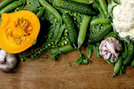 Variety of fresh raw organic vegetables for cooking. Half of hokkaido pumpkin, young green pea, cauliflower, garlic, cucumbers , sprouts over wooden background. Farmer market concept. Flat lay, space 版權商用圖片 - 151509142