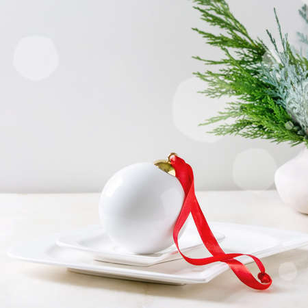 White porcelain Christmas ball with red ribbon in ceramic plate over white marble background. Flat lay, space. Modern Christmas concept.