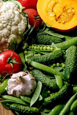 Variety of fresh raw organic vegetables for cooking. Half of hokkaido pumpkin, young green pea, cauliflower, garlic, cucumbers , tomatoes over wooden background. Farmer market concept. Close up