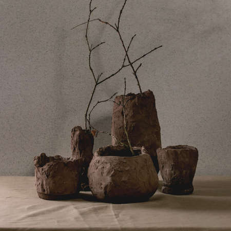 Group of craft handmade raw clay vases with dry branches in interior on table with linen tablecloth and grey wall behind. 版權商用圖片 - 151509132