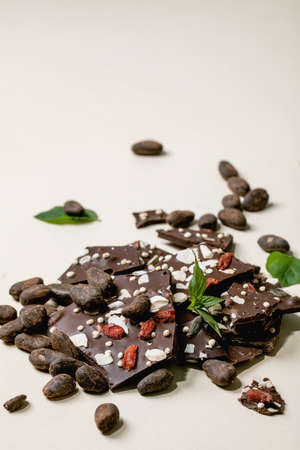 Handmade chopped dark chocolate with different superfood additives seeds and goji berries, with cocoa beans and fresh mint over beige background. 版權商用圖片 - 151509191