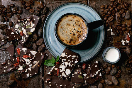 Cup of espresso coffee with jug of milk, handmade dark chocolate, coffee and cocoa beans around over dark ceramic tile as background. Flat lay, copy space