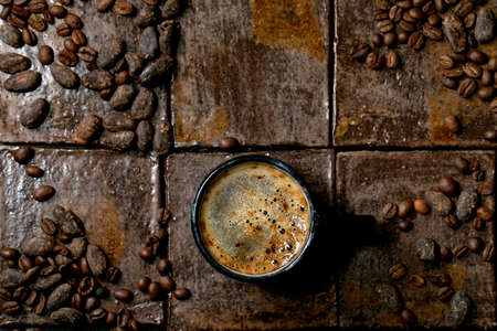 Cup of espresso coffee with coffee and cocoa beans around over dark ceramic tile as background. Flat lay, copy space