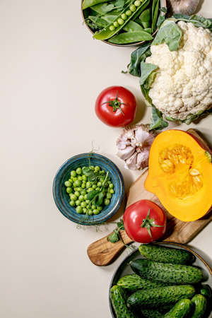 Variety of fresh raw organic vegetables for cooking. Half of hokkaido pumpkin, young green pea, cauliflower, garlic, cucumbers , tomatoes over beige background. Healthy eating concept. Flat lay, space 版權商用圖片 - 151509168