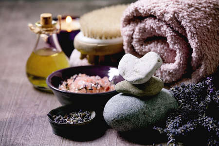 SPA concept. Fresh and dry lavender flowers,stones as heart shape, essential oil, pink salt, bath towel, aromatic candle on textured background. Close up