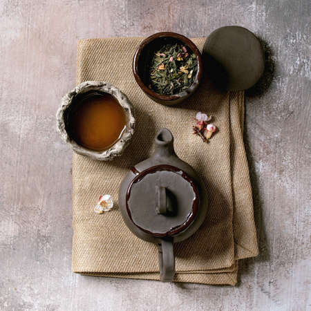 Tea drinking wabi sabi japanese style dark clay cups and teapot on cloth napkin. Grey texture concrete background. Flat lay, space