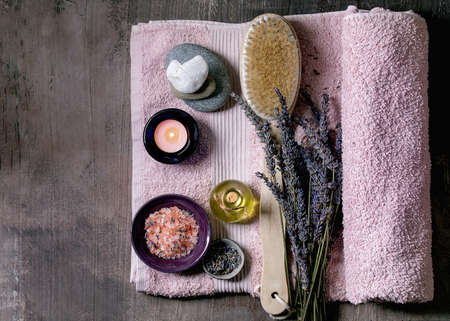 SPA concept. Flat lay of fresh and dry lavender flowers, essential oil, pink salt, stones as heart shape, aromatic candle on pink bath towel over textured background.