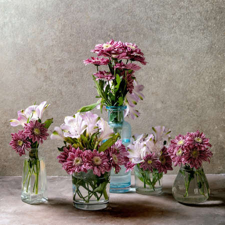 Group of glass bottles and vases with pink decorative flowers bouquets over grey texture background.