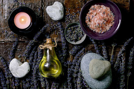 SPA concept. Flat lay of fresh and dry lavender flowers, essential oil, pink salt, stones as heart shape, aromatic candle over dark brown ceramic tile. Stock Photo