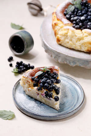 Piece of homemade blueberry baked soft cheesecake san sebastian on ceramic plate, decorated by fresh wild berries, icing sugar and mint over white texture background.