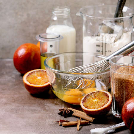 Ingredients for home baking. Flour, eggs, cane sugar, milk in different bowls, blood oranges and spices. Grey texture background 版權商用圖片 - 151691161