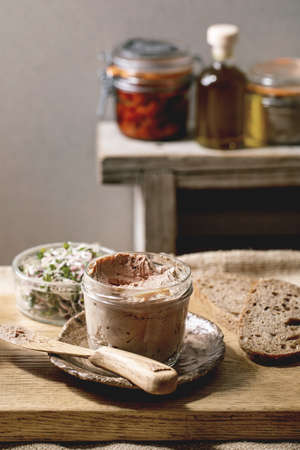Glass jar of homemade chicken liver pate with sliced rye bread, sun-dried tomatoes and green sprout salad on wooden kitchen table. Home breakfast or appetizer
