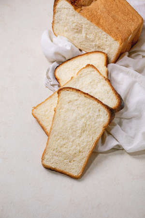 Sliced homemade Hokkaido wheat toast bread on white cloth on white texture background. Flat lay, copy space