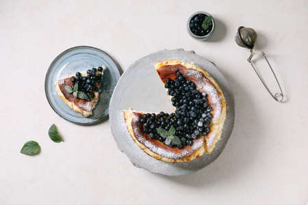Homemade blueberry baked soft cheesecake san sebastian, whole and sliced, on ceramic plate decorated by fresh wild berries, icing sugar and mint over white texture background. Flat lay, space Stock Photo