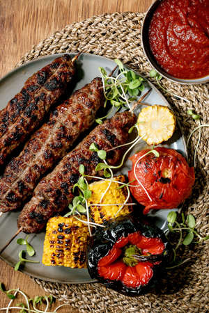Eastern fast food. Grilled spicy beef lyulya kebab on sticks on plate with grilled vegetables sweet corn cob, tomato and paprika, tomato sauce on wooden table. Flat lay 版權商用圖片