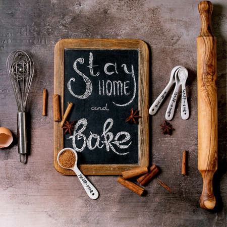 Ingredients and tools for baking. Stay home quarantine isolation period concept. Vintage chalkboard with handwritten chalk lettering Stay home and bake. Grey texture background. Flat lay, space 版權商用圖片 - 151865996