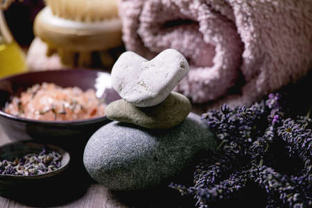 SPA concept. Fresh and dry lavender flowers,stones as heart shape, essential oil, pink salt, bath towel, aromatic candle on textured background. Close up 版權商用圖片 - 151865998