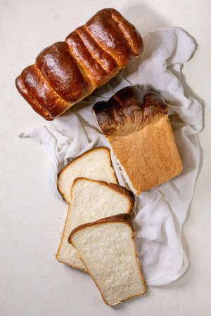Homemade Hokkaido wheat toast bread whole and sliced on white cloth on white texture background. Flat lay, space 版權商用圖片