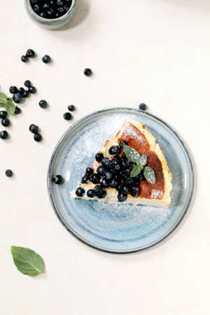 Piece of homemade blueberry baked soft cheesecake san sebastian on ceramic plate, decorated by fresh wild berries, icing sugar and mint over white texture background. Flat lay, space