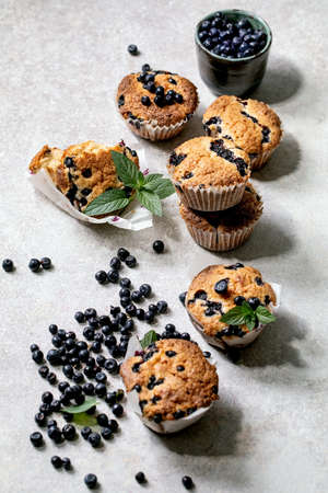 Homemade blueberry muffins in paper cupcake holder decorated by fresh berries and mint leaves on light grey background.