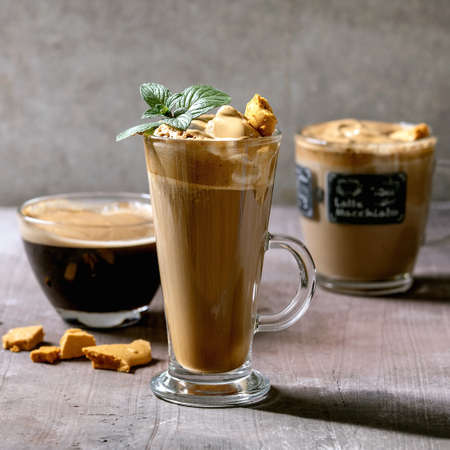 Dalgona frothy coffee trend korean drink latte espresso with coffee foam in three different glass cups, decorated by dalgona cinder toffee candy. Grey concrete background. 版權商用圖片