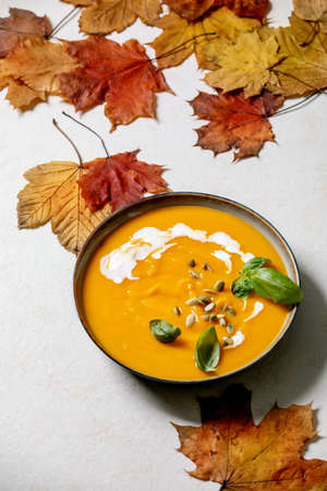 Bowl of pumpkin or carrot vegetarian cream soup decorated by fresh basil, cream and pumpkin seeds on white texture background with yellow autumn maple leaves above. 版權商用圖片