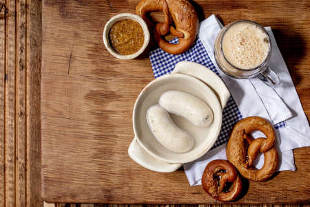 Munich Bavarian traditional white sausages in ceramic pan served with german sweet mustard, mug of dark beer and pretzels bread on white and blue napkin over wooden background. Flat lay, space. 版權商用圖片