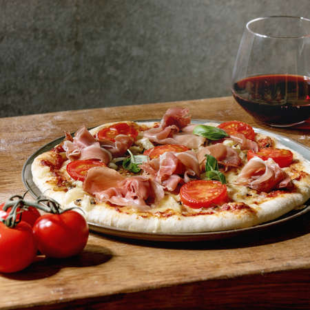 Fresh baking homemade pizza napolitana with prosciutto ham, cheese, tomatoes, basil on plate, glass of red wine over wooden table background. Home baking or delivered fast food.