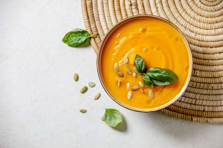 Bowl of pumpkin or carrot vegetarian cream soup decorated by fresh basil, olive oil and pumpkin seeds on white texture background with ingredients above. Flat lay, copy space 版權商用圖片