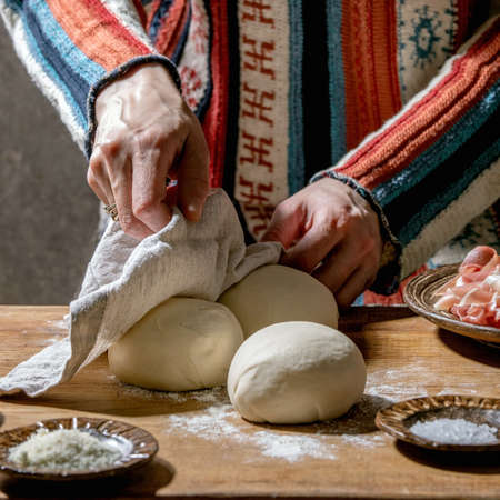 Woman in knitted sweater cooking italian pizza napolitana. Three balls of fresh homemade wheat dough, prosciutto and ingredients in ceramic plates above on wooden kitchen table. Home baking. 版權商用圖片