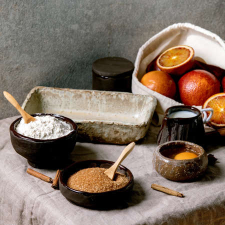 Ingredients for home baking. Flour, eggs, cane sugar, milk in different ceramic bowls, blood oranges and spices on linen table cloth. Grey texture background