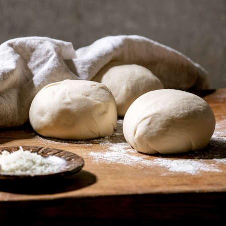 Dough for italian pizza napolitana cooking. Three balls of fresh homemade wheat dough and ingredients in ceramic plates above on wooden kitchen table. Home baking. 版權商用圖片