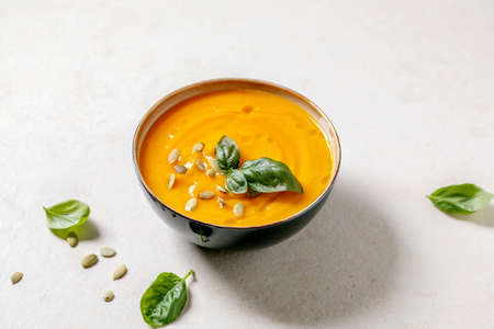 Bowl of pumpkin or carrot vegetarian cream soup decorated by fresh basil, olive oil and pumpkin seeds on white texture table with ingredients above. 版權商用圖片