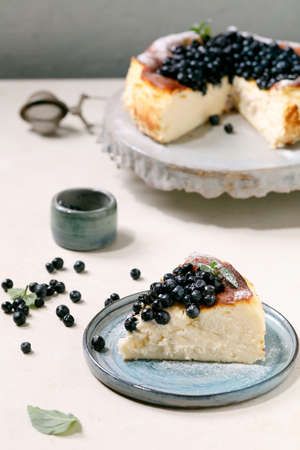 Homemade blueberry baked soft cheesecake san sebastian, whole and sliced, on ceramic cake stand plate decorated by fresh wild berries, icing sugar and mint over white texture background.