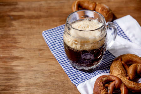 Glass of lager beer with traditional salted pretzels on white and blue napkin over wooden background. Oktoberfest theme 版權商用圖片