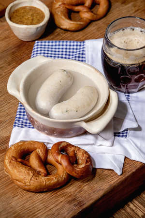 Munich Bavarian traditional white sausages in ceramic pan served with german sweet mustard, mug of dark beer and pretzels bread on white and blue napkin over wooden table.