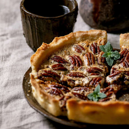 Pieces of home baking classic american pecan caramel pie on ceramic plate, coffee cup, cezve, jug of cream on gray linen table cloth.. 版權商用圖片