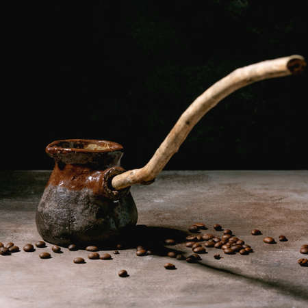 Black turkish coffee in craft handmade ceramic coffee pot cezve with long wooden handle with coffee beans above. Grey texture background. Copy space