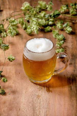Classic glass mug of fresh cold foamy lager beer with green hop cones behind over wooden texture background. Copy space 版權商用圖片