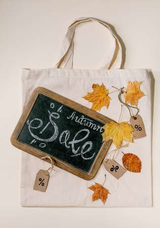 Autumn sale concept. Vintage chalkboard with hand written lettering Sale, labels with percents, yellow autumn leaves on eco linen shopping bag over beige background. Flat lay. Stock Photo