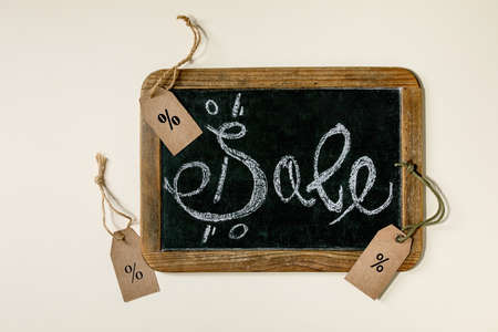Promotion sale concept. Vintage chalkboard with hand written chalk lettering Sale, labels with percents over beige background. Flat lay.