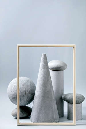 Abstract background with composition of different grey geometric objects, picture frame and stones. Copy space. Modern concept for product presentation.