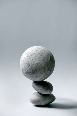 Abstract background with composition of balanced grey geometric objects sphere and stones. Copy space. Modern concept for product presentation. Stock Photo