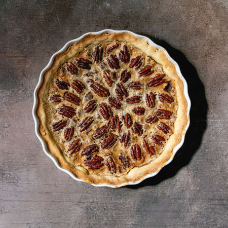 Fresh home baking classic american pecan caramel pie in white ceramic baking dish over grey texture background. Flat lay, space